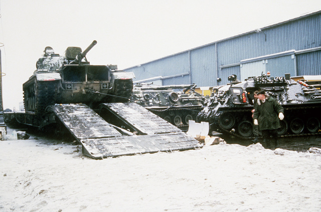 An M60A1 main battle tank is pulled off a flatbed railroad car by a Leopard armored recovery vehicle during Exercise REFORGER'85