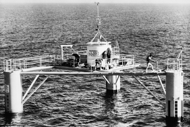 Personnel from the Naval Civil Engineering Laboratory finish readying instrumentation inside the circular deck house on a semisumbersible laboratory moored off the Southern California coast