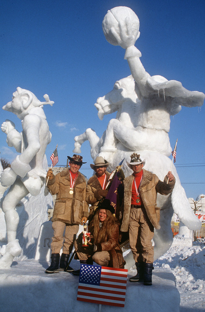 "Members of the 1985 US Olympic Snow Sculpting Team, Yokota Air Base, Japan, pose in front of their winning sculpture: ""Icabod Crane and the Headless Horseman,"" at the close of the 12th International Snow Statue Contest"