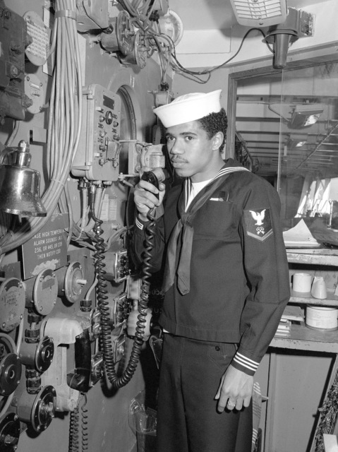 A crewman speaks into a microphone while at his station aboard the repair ship USS AJAX (AR 6)