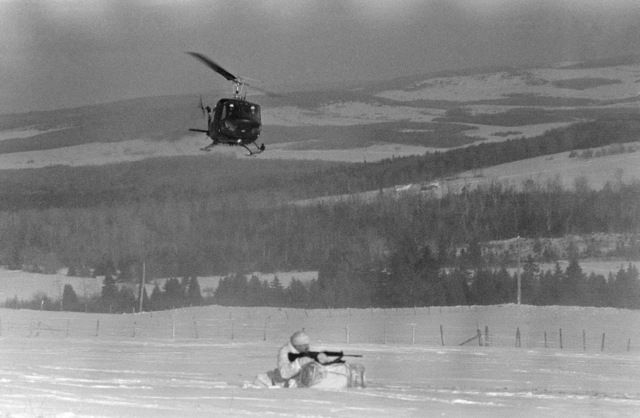 A Canadian infantryman sets up in a defensive firing position after being brought in aboard a CH-135 Iroquois helicopter, overhead, during the joint US/Canadian Operation NEZ ROUGE'85 being held in the province of Quebec