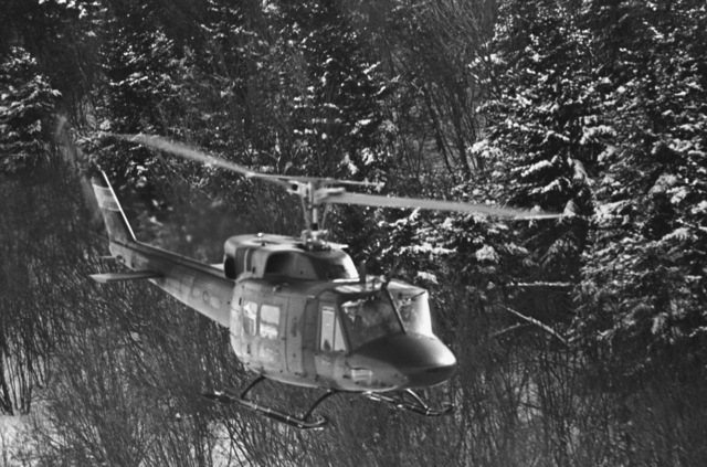 An air-to-air right front view of a Canadian CH-135 Iroquois helicopter in flight over a wooded area during the joint US/Canadian operation NEZ ROUGE'85 being held in the province of Quebec