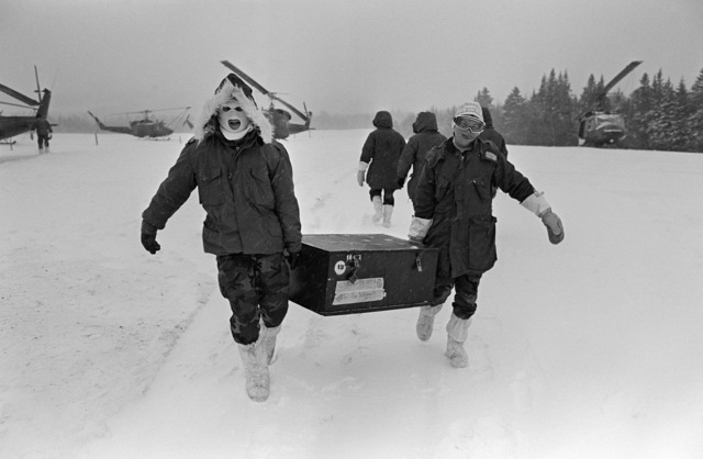 Marines from Marine Light Helicopter Squadron 771 (HML-771) carry mount-out boxes from UH-1N Iroquois helicopters to their command post during the joint US/Canadian Operation NEZ ROUGE'85 being held in the province of Quebec