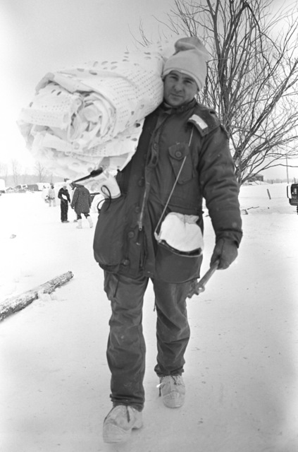 MASTER Sergeant (MSGT) Tom Constantine, Marine Light Helicopter Squadron 771 (HML-771), carries tent camouflage during the joint US/Canadian operation NEZ ROUGE'85 being held in the province of Quebec