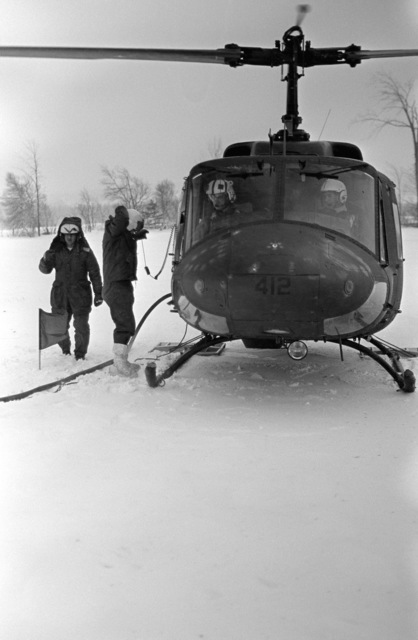 Members of Marine Light Helicopter Squadron 771 (HML-771) refuel a UH-1N Iroquois helicopter during the joint US/Canadian Operation NEZ ROUGE'85 being held in the province of Quebec