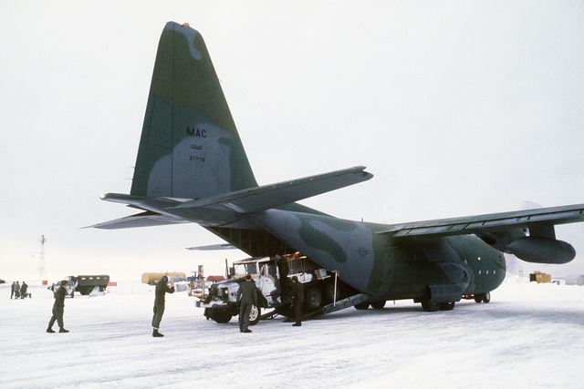 A cargo truck is unloaded from a C-130 Hercules aircraft during Exercise BRIM FROST '85