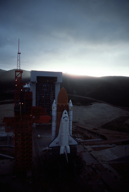 """A high angle, pre-sunrise overall view of the Space Shuttle Enterprise in launch position on the Space Launch Complex (SLC) #6, commonly known as """"SLICK 6"""", during the ready-to-launch checks to verify launch procedures. Exact Date Shot Unknown"""