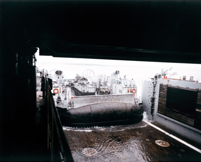 A landing craft air cushion (LCAC 001) enters the well deck of the dock landing ship USS PENSACOLA (LSD 38) during the first underway mating of an LCAC and LSD. The LCAC is carrying an M-151 light utility vehicle, an LAV 25 light armored vehicle and an M-60 tank