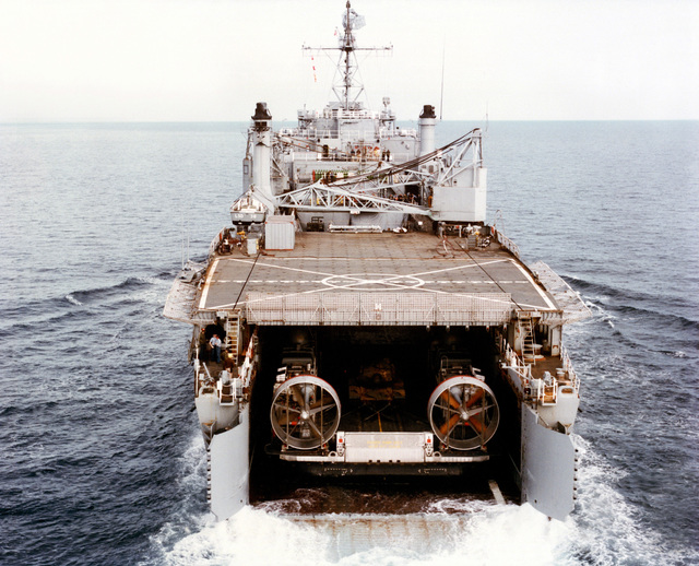 A stern view of a landing craft air cushion (LCAC 001) in the well deck of the dock landing ship USS PENSACOLA (LSD 38) after completing the first underway mating of an LCAC and an LSD. An M-60 tank is secured in the cargo area of the LCAC