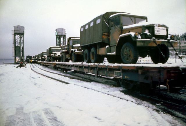 A U.S. Army M-939 5-ton cargo truck, in front, and other military transport vehicles are transported to Anchorage on the Alaskan Railroad Hydrotrain during Exercise Brim Frost ''85