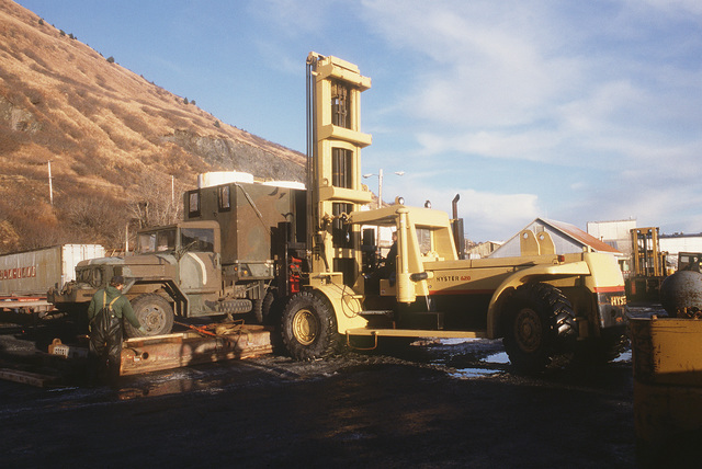 A US Army M35 2 1/2-ton cargo truck is unloaded with a forklift on pier No. 2. The truck will be used for Exercise BRIM FROST '85