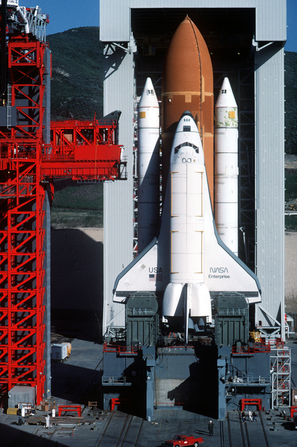 A view of the space shuttle Enterprise, mated to an external fuel tank and solid rocket boosters, resting on the launch mount next to the access tower at Space Launch Complex Six. The mobile service tower is in the background