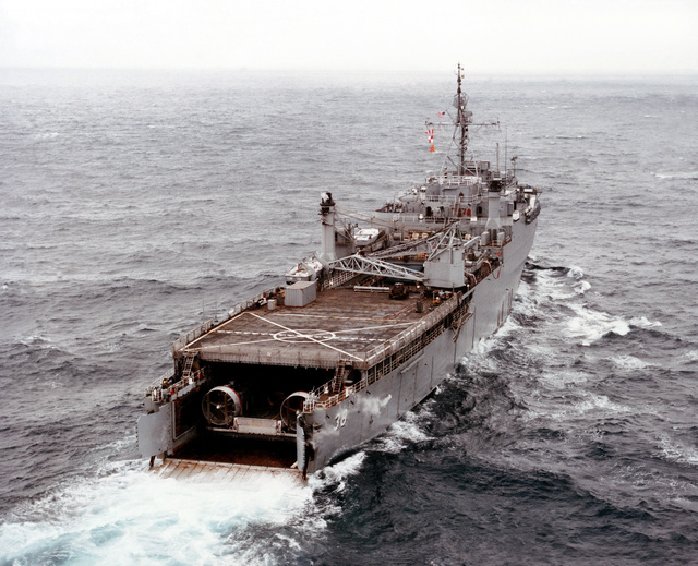 An elevated starboard quarter view of a landing craft air cushion (LCAC 001) in the well deck of the dock landing ship USS PENSACOLA (LSD 38) after completing the first underway mating of an LCAC and an LSD