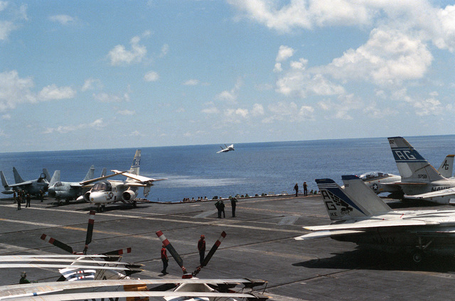 An F-14A Tomcat aircraft approaches for a low-level pass by the nuclear-powered aircraft carrier the USS DWIGHT D. EISENHOWER (CVN 69).  On deck aboard the EISENHOWER are various aircraft including A-7E Corsair IIs, an S-3A Viking and F-14A Tomcats