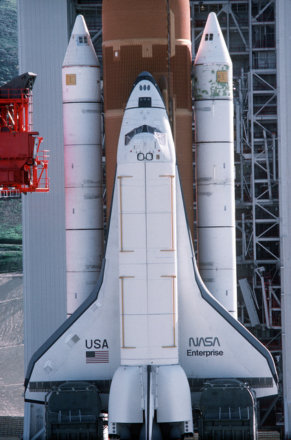 """High angle close-up view of Space Shuttle Enterprise in launch position on the Space Launch Complex (SLC) #6, commonly known as """"SLICK 6"""", during the ready-to-launch checks to verify launch procedures. Exact Date Shot Unknown"""
