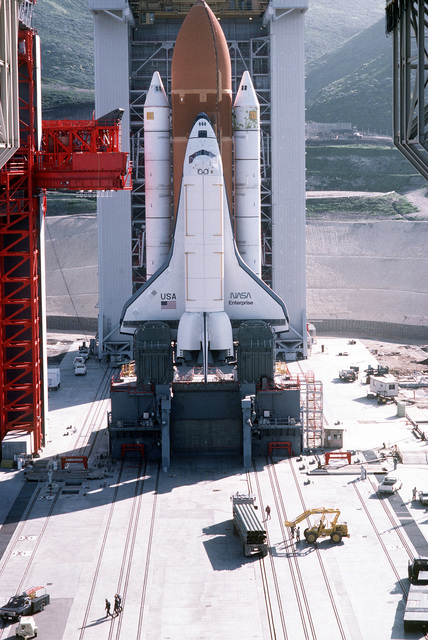 """High angle view of Space Shuttle Enterprise in launch position on the Space Launch Complex (SLC) #6, commonly known as """"SLICK 6"""", during the ready-to-launch checks to verify launch procedures. Exact Date Shot Unknown"""
