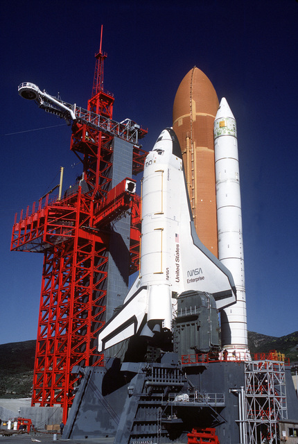"""Low angle view of gantry and Space Shuttle Enterprise in launch position on the Space Launch Complex (SLC) #6, commonly known as """"SLICK 6"""", during the ready-to-launch checks to verify launch procedures. Exact Date Shot Unknown"""