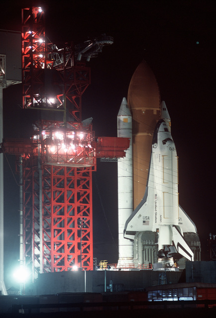 """Night view of shelter, gantry and Space Shuttle Enterprise in launch position on the Space Launch Complex (SLC) #6, commonly known as """"SLICK 6"""", photographed through the shelter building. Exact Date Shot Unknown"""