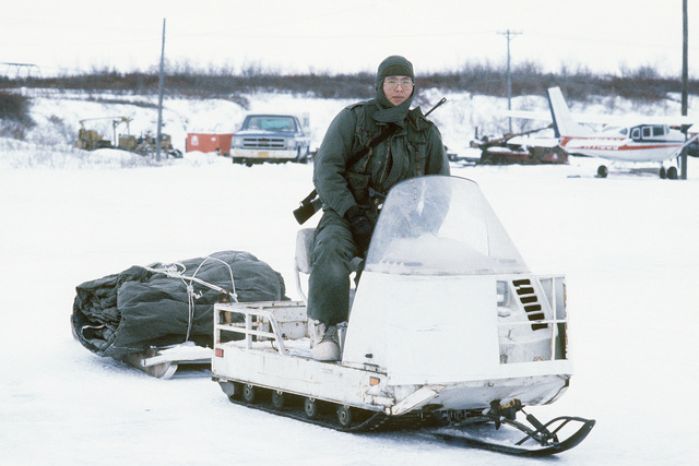Sergeant (SGT) Duane Lincoln, 292nd Scout Group Headquarters, waits to load his snowmobile and sled onto a 17th Tactical Airlift Squadron C-130 Hercules aircraft. The C-130 is flying support for the Scout Group from Nome to Unalakeet, Alaska, during Exercise BRIM FROST '85