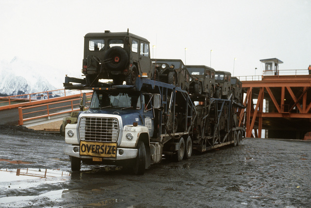 US Army M151 1/4-ton light vehicles are being taken to Anchorage by trailer during Exercise BRIM FROST '85