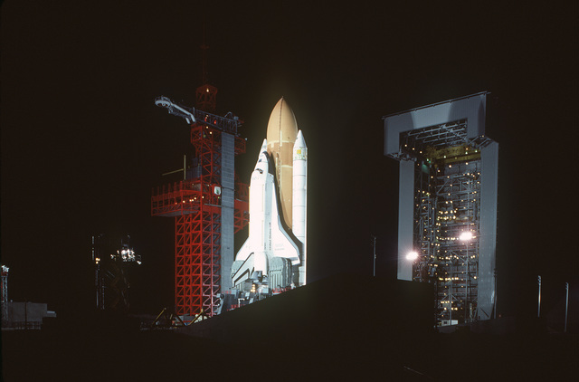 A nighttime view of the space shuttle Enterprise, mated to an external tank and solid rocket boosters, resting on the launch mount next to the access tower at Space Launch Complex Six. The mobile service tower is on the right