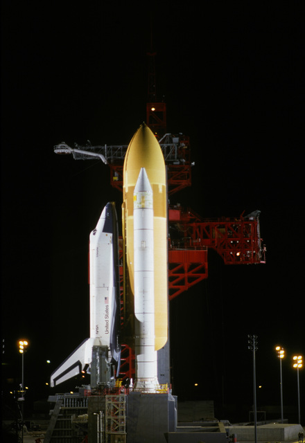 A nighttime view of the space shuttle Enterprise, mated to an external tank and solid rocket boosters, resting on the launch mount next to the access tower at Space Launch Complex Six