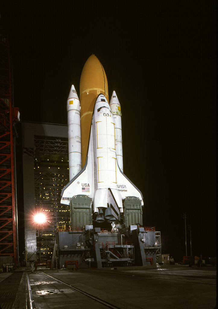 A nighttime view of the space shuttle Enterprise, mated to an external tank and solid rocket boosters, resting on the launch mount next to the access tower at Space Launch Complex Six. The mobile service tower is in the background