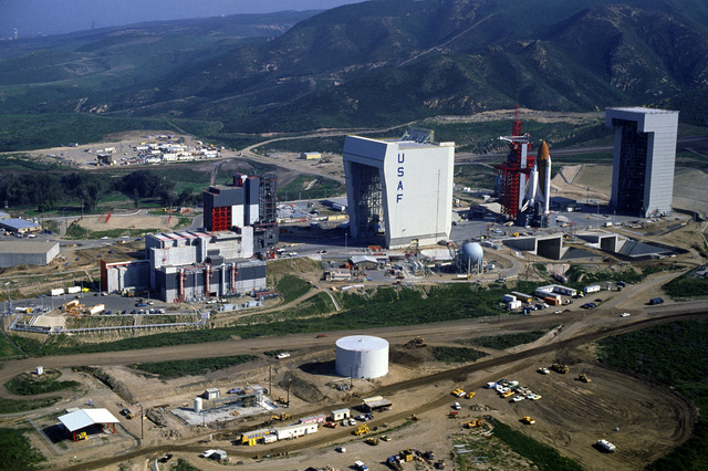 An overall view of Space Launch Complex Six. The structures are, from left to right: the payload changeout room attached, the shuttle assembly building, the access tower and launch mount, and the mobile service tower. The space shuttle Enterprise, mated to an external tank and solid rocket boosters, is resting on the launch mount
