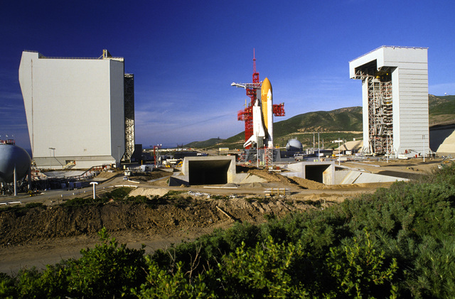 The space shuttle Enterprise, mated to an external tank and solid rocket boosters, rests on the launch mount next to the access tower at Space Launch Complex Six. The shuttle assembly building is on the left and the mobile service tower is on the right