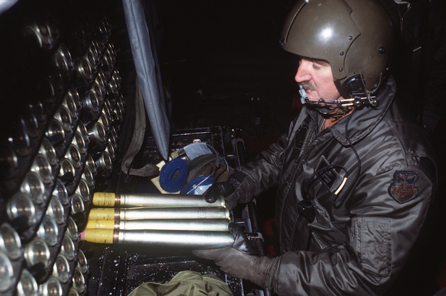A member of the 16th Special Operations Squadron loads 40 mm rounds into a rack aboard an AC-130H Hercules aircraft during Exercise BRIM FROST '85