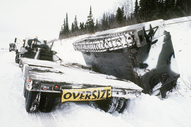 A US Army M113 armored personnel carrier overturned from a flatbed truck during Exercise BRIM FROST '85