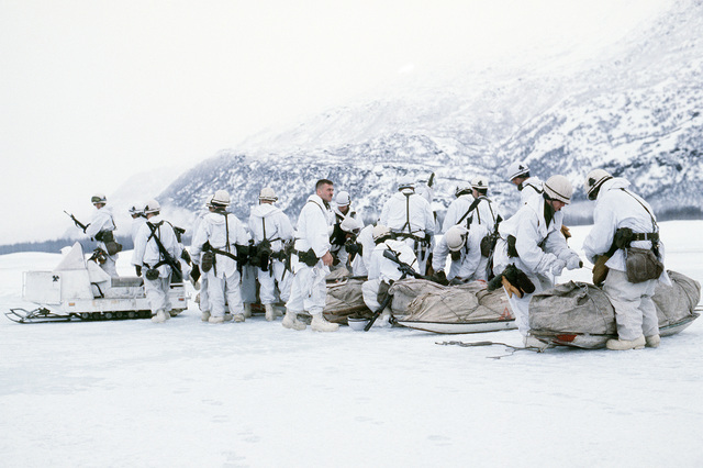 Army personnel from Company C, 5th Battalion, 377th Infantry Brigade, Fort Richardson, Alaska, load their equipment and onto sled and snowmobiles during Exercise BRIM FROST '85