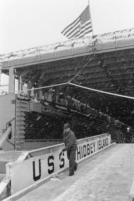 Crewmen clear snow from the brow of the dock landing ship USS WHIDBEY ISLAND (LSD 41) prior to the arrival of guests for the commissioning ceremony. The ceremony is being held in the well deck