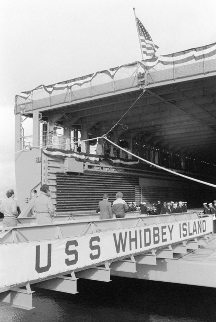 Guests cross the brow of the dock landing ship USS WHIDBEY ISLAND (LSD 41) prior to the beginning of its commissioning ceremony. The ceremony is being held in the well deck of the ship, docked at Lockheed Shipyard