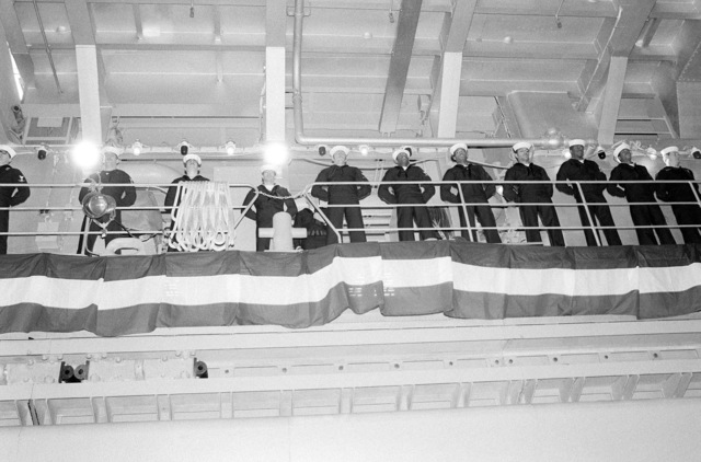 Members of the crew man the rail around the well deck of the dock landing ship USS WHIDBEY ISLAND (LSD 41) during its commissioning ceremony. The ceremony is being held at Lockheed Shipyard