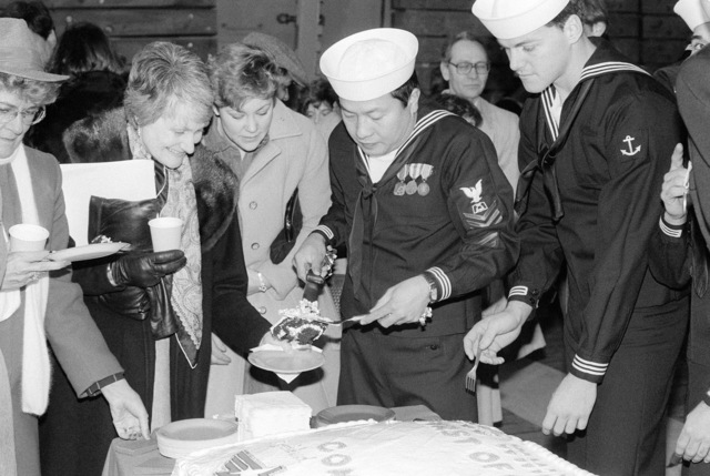 Mess Management SPECIALIST First Class Romeo Magtoto, left, serves the cake at the reception following the commissioning for the dock landing ship USS WHIDBEY ISLAND (LSD 41)