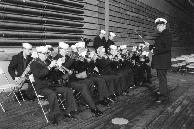 The Navy Band, Seattle, plays during the commissioning ceremony for the dock landing ship USS WHIDBEY ISLAND (LSD 41). The ceremony is being held in the well deck of the ship