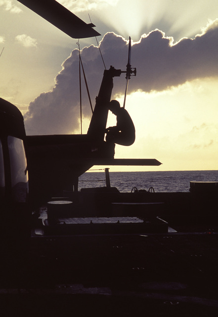 An Army helicopter crewman performs preflight maintenance on a UH-1 Iroquois helicopter aboard the battleship USS IOWA (BB 61). The ship has embarked local Army helicopter detachments to provide aerial logistic support during its deployment to Central America