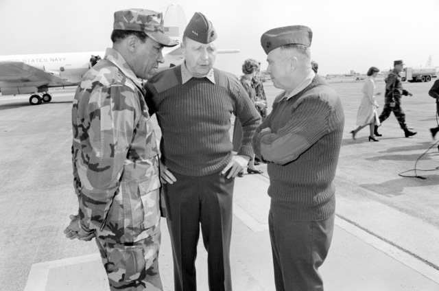Major General (MGEN) Frank E. Peterson Jr., left, commanding general of the First Marine Aircraft Wing; Lieutenant General (LGEN) Charles G. Cooper, center, commanding general, Fleet Marine Force Pacific; and Colonel (COL) D.J. McCarthy, right, commanding officer, MCAS Iwakuni talk on the flight line during Cooper's visit