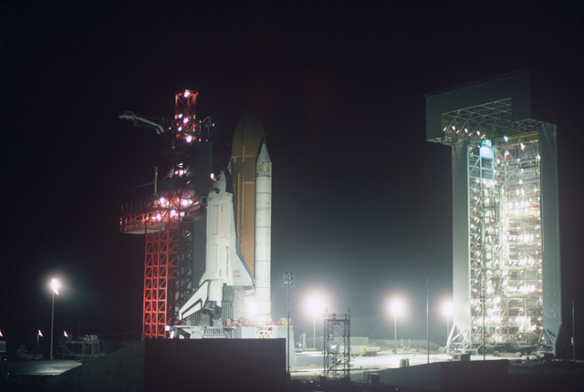 A nighttime view of the National Aeronautics and Space Administration Orbiter OV-101 Enterprise on the launch tower as it would appear prior to launch. The Enterprise is not equipped to be launched but is being used as a model at the newly constructed space shuttle launch facilities