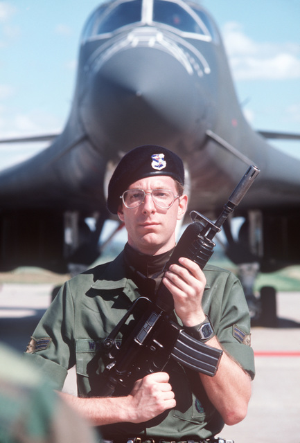 AIRMAN First Class Peter Warner, 3902nd Air Base Wing, Security Police Squadron, Wheaton, Illinois, provides security for a B-1B bomber aircraft (background) during a stopover. He is armed with an M16A1 carbine