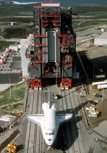 An overhead view of the space shuttle Enterprise moving toward the shuttle assembly building at Space Launch Complex Six aboard its specially-designed 76-wheel transporter. In the background are the payload changeout room and the payload preparation room