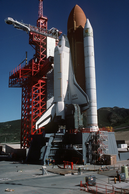 The space shuttle Enterprise, mated to an external tank and solid rocket boosters, rests on the launch mount next to the access tower at Space Launch Complex Six