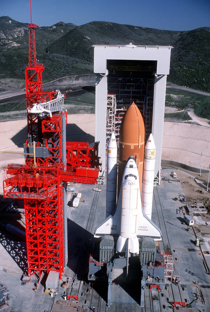 The space shuttle Enterprise, mated to an external tank and solid rocket boosters, rests on the launch mount next to the access tower at Space Launch Complex Six. In the background is the mobile service tower