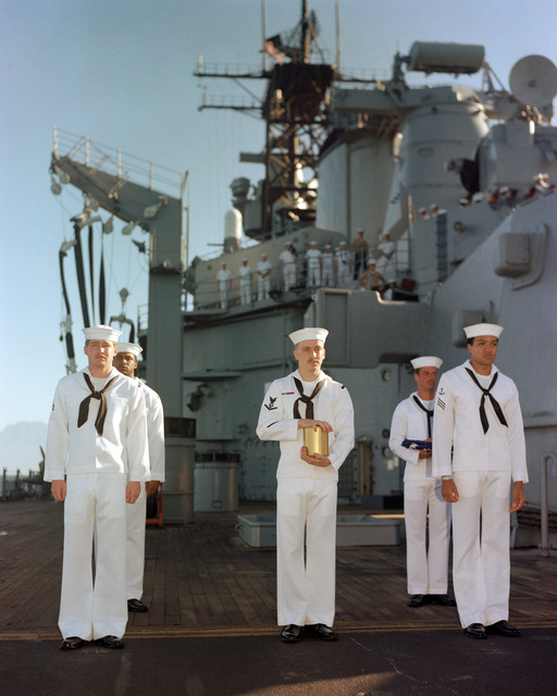 Central America. Members of a burial-at-sea detail stand at attention aboard the battleship USS IOWA (BB 61). The sailor in the center is holding an urn containing the ashes of the deceased