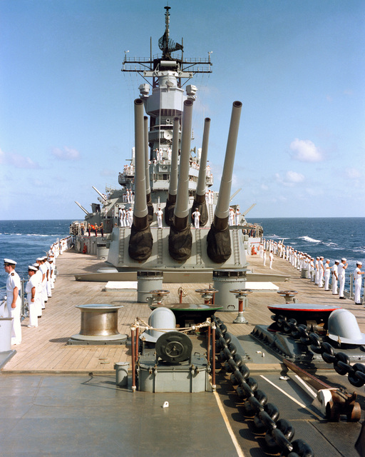 Crew members man the rail aboard the battleship USS IOWA (BB 61) during a pass in review ceremony for officials of the Central America nation of Belize