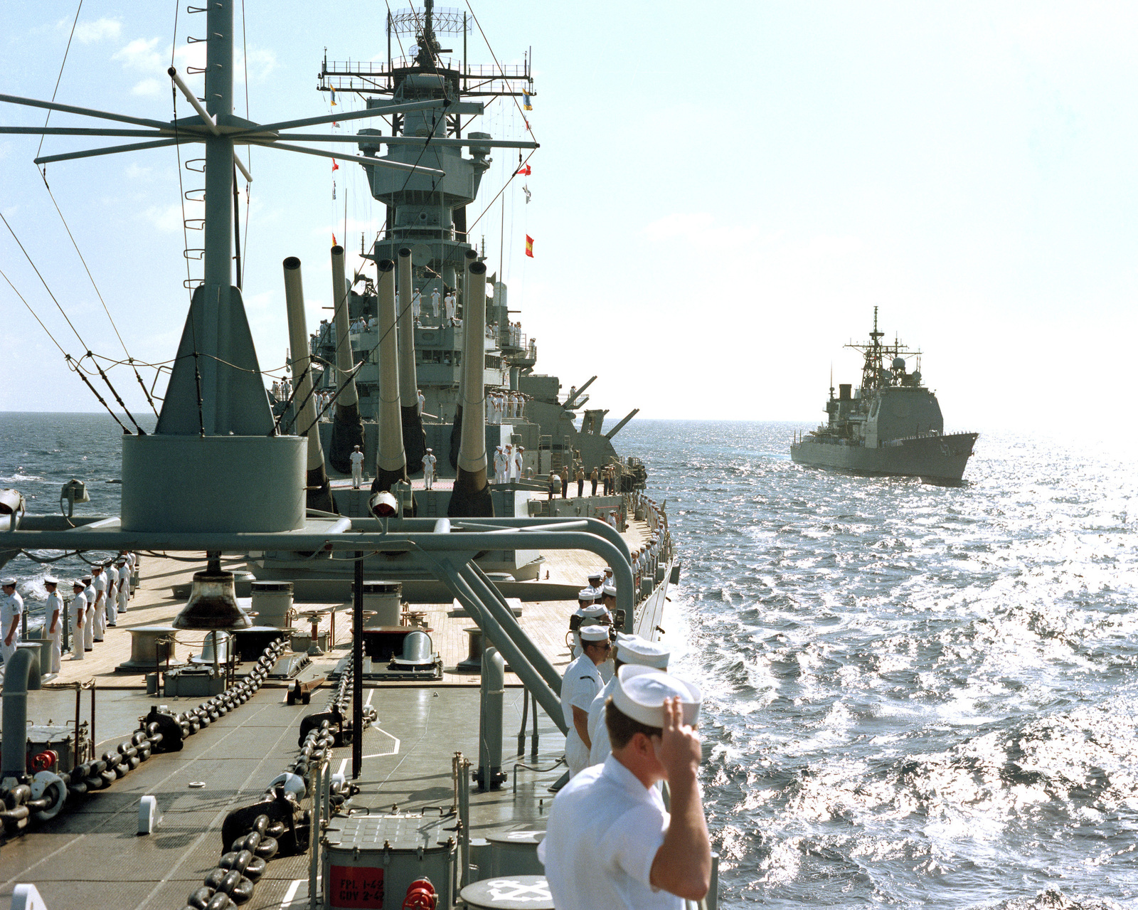 Crew members man the rail aboard the battleship USS IOWA (BB 61) during a pass in review ceremony for officials of the Central America nation of Belize. On the right is the guided missile cruiser USS TICONDEROGA (CG 47)