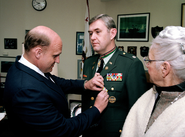 Richard L. Armitage, Assistant Secretary of Defense for International Security Affairs, presents the Defense Superior Service Medal to Lieutenant Colonel Benedict F. FitzGerald, Country Director for Jordan, Syria and Lebanon, during a ceremony at the Pentagon. FitzGerald's mother is at right