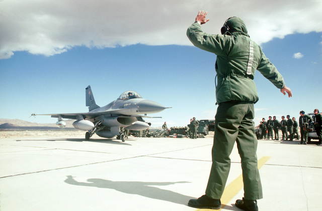 A 388th Tactical Fighter Wing F-16A Fighting Flacon aircraft is guided into the live ordnance area of the flight line during Exercise LEADING EDGE II
