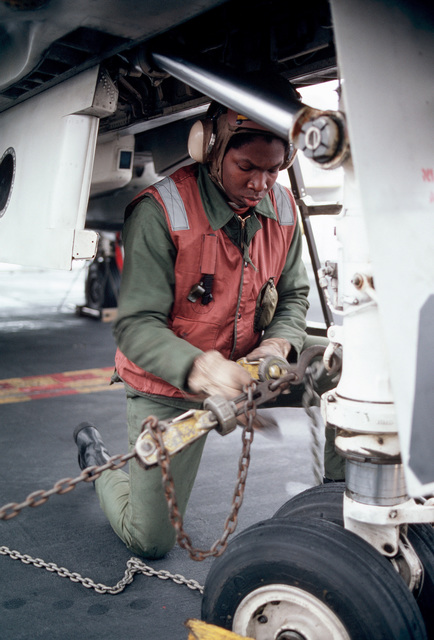 A crewman tightens an aircraft tie down chain aboard the aircraft carrier USS MIDWAY (CV 41)